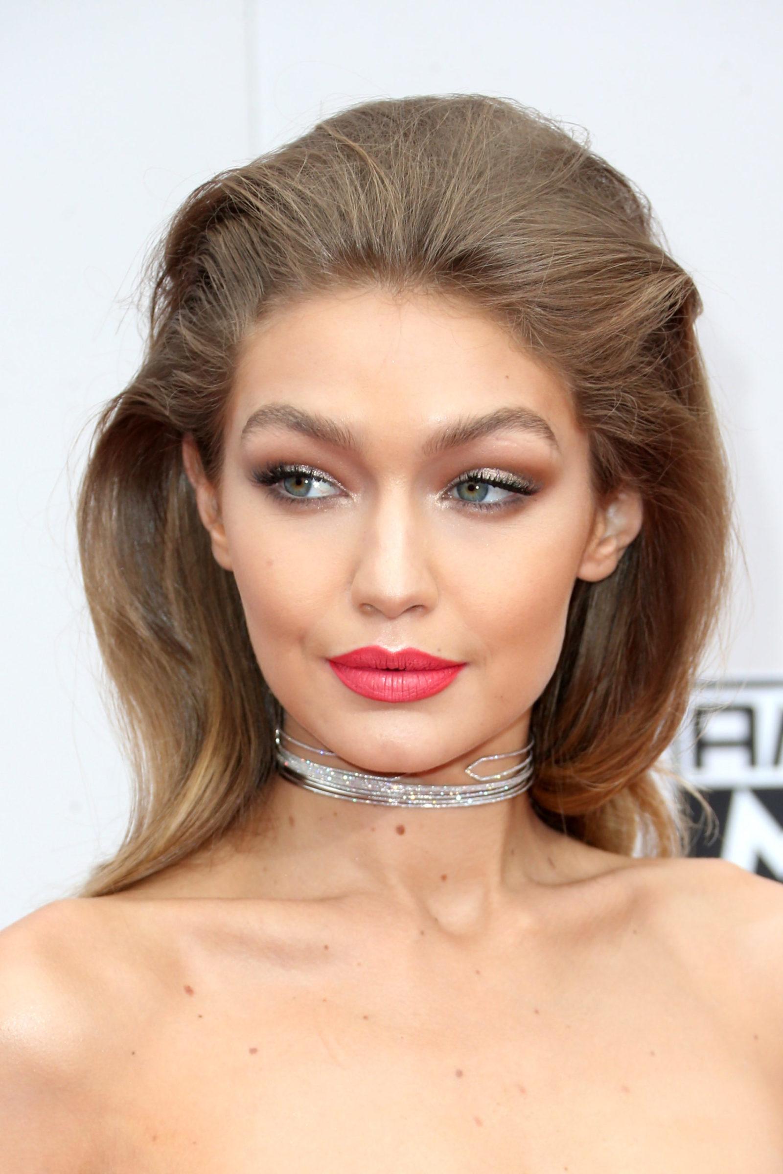 Gigi Hadid com make bela e iluminada em tons de marrom + batom coral e cabelo bafo todo para trás com volume