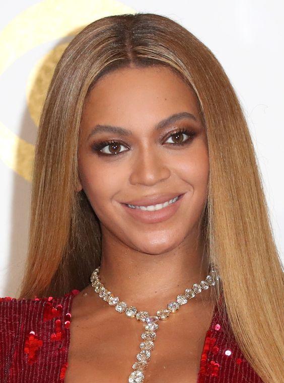 Beyoncé com esfumado marrom belo e destaque nos cílios + cabelo lisão com risca no meio