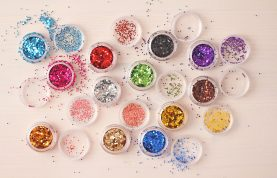 Multi-colored Sequins for the design of nails in a box. Glitter in jars. Foil for nail service. Photo set. Sparkling beauty shimmer, glitter